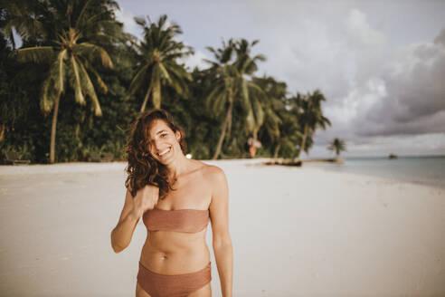 Portrait of happy woman on the beach, Maguhdhuvaa Island, Gaafu Dhaalu Atoll, Maldives - DAWF01229