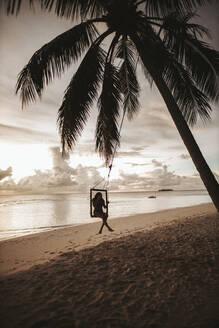 Woman on a swing at the sea at sunset, Maguhdhuvaa Island, Gaafu Dhaalu Atoll, Maldives - DAWF01232