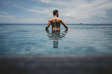 Rear view of man relaxing in infinity pool, Maguhdhuvaa Island, Gaafu Dhaalu Atoll, Maldives - DAWF01247