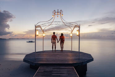 Couple standing on jetty at the sea at sunset, Maguhdhuvaa Island, Gaafu Dhaalu Atoll, Maldives - DAWF01256
