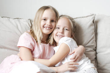 Portrait of two little girls hugging each other on the couch - EYAF00917