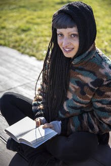 Portrait of smiling young woman with piercings and braids sitting on bench with a book, Como, Italy - MCVF00202