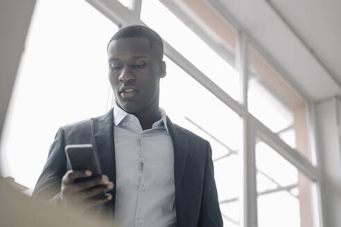Portrait of young businessman standing in front of window looking at cell phone - KNSF07422
