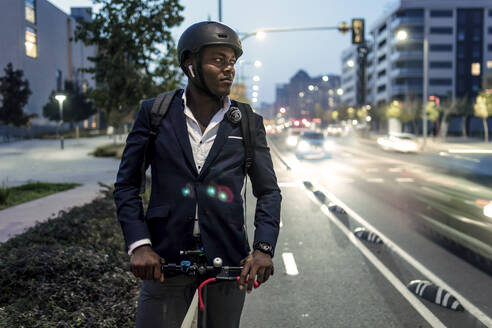 Portrait of businessman with push scooter on bicycle lane in the evening - JSRF00803