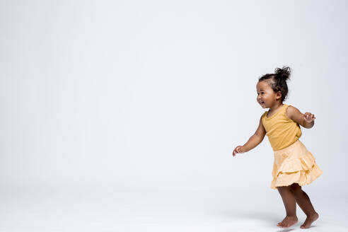 Happy little girl running barefoot in front of grey background - DAWF01262