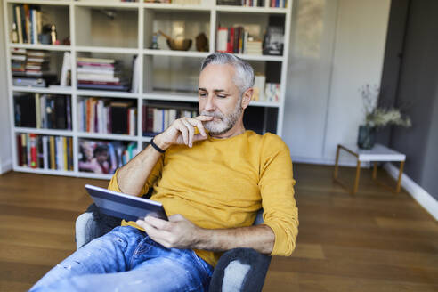 Relaxed mature man at home using tablet - FMKF06110