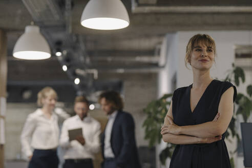 Portrait of confident businesswoman in office with colleagues in background - KNSF07480