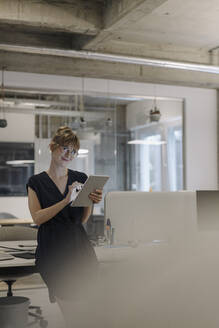 Confident businesswoman using tablet in office - KNSF07486