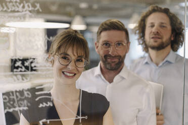 Portrait of confident business team behind a glass pane in office - KNSF07498