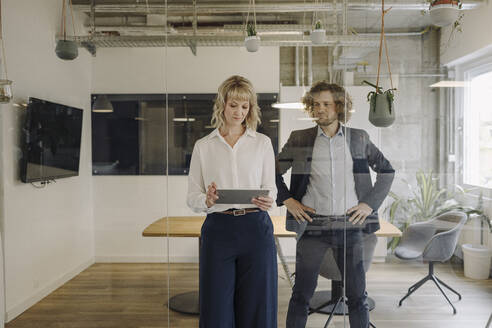 Businessman and businesswoman using tablet in office - KNSF07516