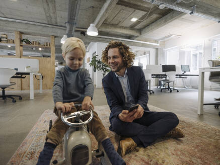 Smiling businessman with son on toy car in office - KNSF07519