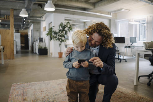Businessman with son in office using cell phone - KNSF07534