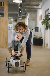 Businessman pushing son on toy car in office - KNSF07537