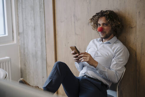Portrait of businessman with red clown nose using cell phone in office - KNSF07591