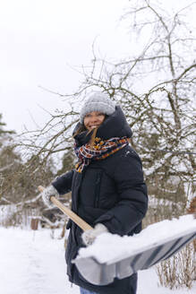 Portrait of smiling woman with snow shovel - KNTF04171