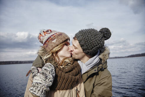 Young couple kissing in front of a lake - ANHF00160