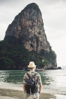 Woman looking at rock on the beach of Railay, Krabi, Thailand - CHPF00601
