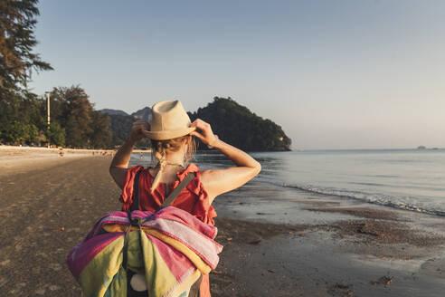 Rear view of woman on the beach at sunset, Noppharat Thara Beach, Ao Nang, Krabi, Thailand - CHPF00604