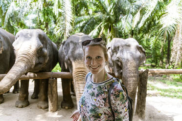 Portrait of smiling woman with elephants in sanctuary, Krabi, Thailand - CHPF00607