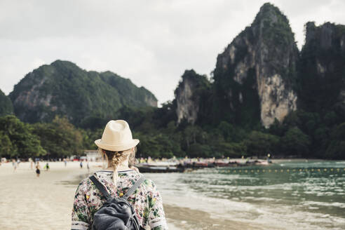 Woman looking at rock on the beach of Railay, Krabi, Thailand - CHPF00613