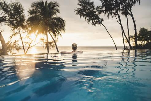 Rear view of woman in infinity pool at sunset, Nai Thon Beach, Phuket, Thailand - CHPF00619