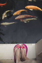 Close-up of woman in flip flops standing at a pool with kois - CHPF00628