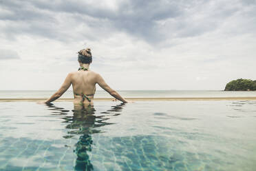 Rear view of woman in infinity pool, Koh Lanta, Thailand - CHPF00631
