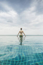 Rear view of woman in infinity pool, Koh Lanta, Thailand - CHPF00634