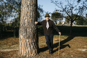 Old man with cane, leaning on tree in park - JRFF04103