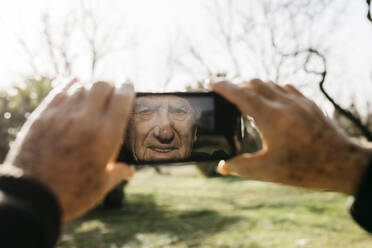 Old man taking pictutes with his smartphone - JRFF04112