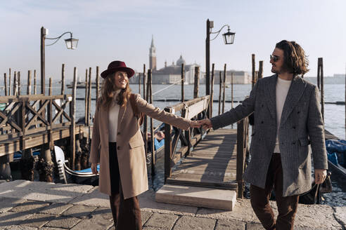 Young couple walking hand in hand at the waterfront in Venice, Italy - MAUF03261