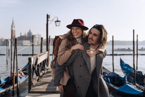 Young man giving his girlfriend a piggyback ride at the waterfront in Venice, Italy - MAUF03264