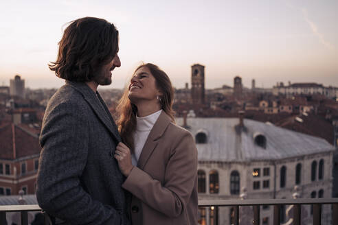 Happy young couple on a balcony above the city of Venice, Italy - MAUF03309