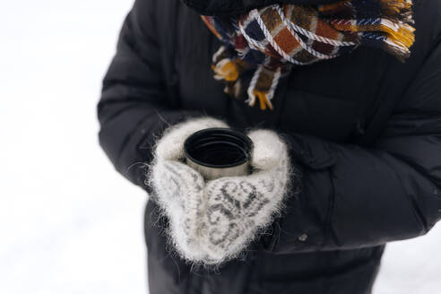 Woman's hands holding thermo mug outdoors - KNTF04198