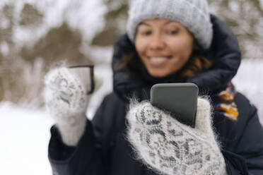 Woman with thermo mug taking selfie with smartphone in winter - KNTF04201