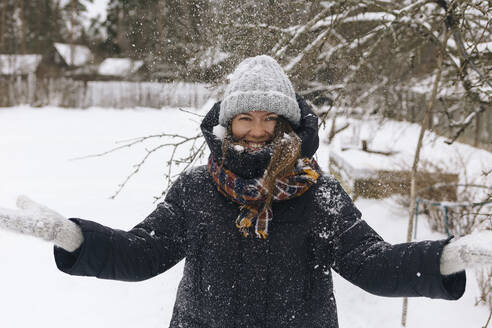 Portrait of woman enjoying snowfall - KNTF04207