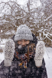 Portrait of woman enjoying snowfall - KNTF04210