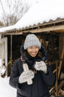 Portrait of happy woman with thermo flask in winter - KNTF04213
