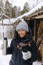 Portrait of happy woman with thermo flask in winter - KNTF04216