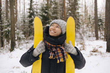 Portrait of smiling woman with skis in winter forest - KNTF04224