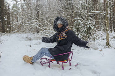 Smiling woman sitting on sledge throwing snow into the air in winter forest - KNTF04230
