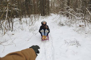 Man's hand pulling woman sitting on a sledge - KNTF04233