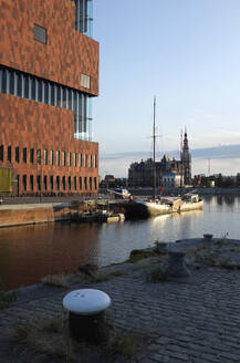 Belgium, Antwerp, Museum aan de Stroom (MAS) by river with Maison Mason in background, sunset - GISF00511