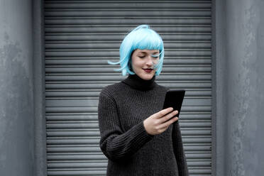 Young woman wearing blue wig and using smartphone - FLLF00387