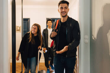 Smiling young friends arriving with luggage at rental apartment - MASF16448