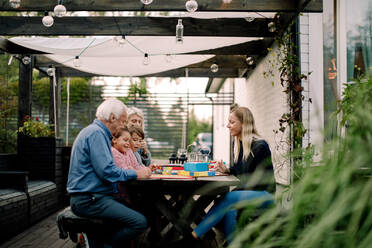 Smiling family playing board game while sitting at table in patio - MASF16463