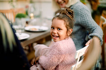 Portrait of smiling girl sitting with grandmother by dining table during lunch - MASF16472
