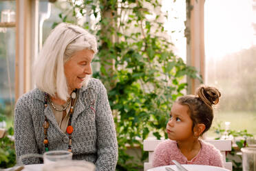 Smiling grandmother looking at granddaughter while having lunch - MASF16475