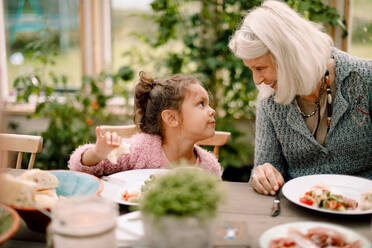 Smiling grandmother looking at granddaughter while sitting by dining table during lunch - MASF16484