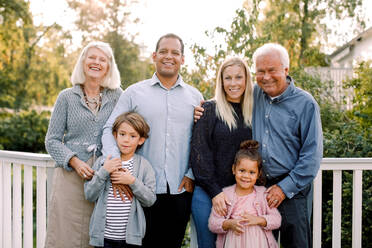 Portrait of smiling multi-generation family standing against railing in backyard - MASF16493
